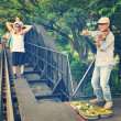 Violinist on the bridge of the river kwai, Kanchanaburi of Thailand. — Stock Photo