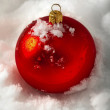 Photo: One red Christmas ball on the snow