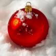 une boule de Noël rouge sur la neige — Photo