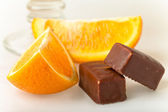 Two chocolates with orange slice close-up on white background — Stock Photo
