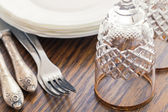 Pile of clean white plates and wine glasses on the table — Stock Photo