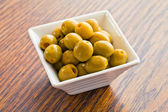 Olives in a white bowl on wooden table — Stock Photo