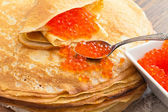 Pancakes with a spoon of red caviar — Stock Photo