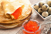 Pancakes with caviar and quail eggs — Stock Photo