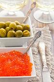 Aceitunas y caviar rojo se encuentran en dos cuencos blancos — Foto de Stock