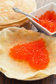 Pancakes with red caviar in a heart shape — Stock Photo
