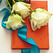 Notebook in orange leather cover with white roses as gift — Stock Photo #21687345
