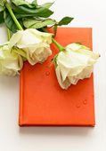Notebook in orange leather cover with white roses as a gift — Stock Photo