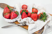 Strawberries on board cutting on striped napkin — Stock Photo