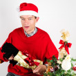 Stock Photo: Min red sweater unwrapping Christmas gift