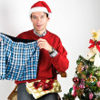 Stock Photo: Munwrapping Christmas gift