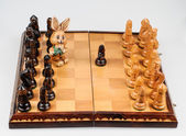 Carved hare among the chess pieces — Stock Photo