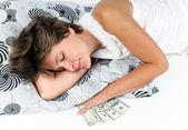 Yastığın altına para ile uyuyan kadın — Stok fotoğraf