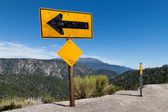 Arrow sign on top of high altitude cliff — Stock Photo