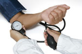Doctor measuring blood pressure on white background — Stock Photo