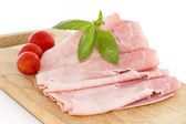 Baked ham with slices and tomatoes on wooden board — Stock Photo