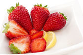 Strawberries and Lemmon in white plate — Stock Photo