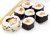 Delicious sushi rolls on white plate with chopsticks — Stock Photo