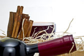 Red wine bottle with a glass and cinnamons — Stock Photo