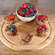 Mixed muffins fruits on wooden board — Stock Photo #25551219