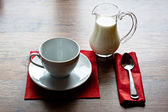 Jug of milk with a empty cup on old wooden table — Stock Photo