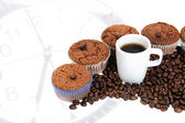 Coffee Muffins with a cup of coffee on clock's background — Stock Photo