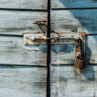 Rusty padlock on an old wooden door — Stock Photo