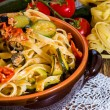 Pasta with vegetables in ceramic clay pot — Stock Photo