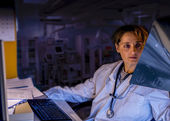 Tired Doctor looking x ray  at night duty — Stock Photo