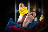 Feet on the sofa with a post card — Stock Photo