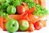 Green tomatoes in the orange basket — Stock Photo