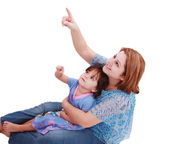 Happy mother and little daughter sit down and point fingers up — Stock Photo