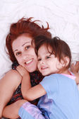 Closeup of mother and daughter lying down looking up — Stock Photo
