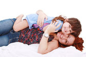Happy young mother playing with her daughter on the bed at home — Stock Photo