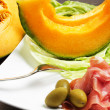 Melon with ham on the table - Stock Photo