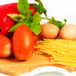 Spaghetti, pasta on the table with eggs, tomatoes and peppers on a white background — Stock Photo