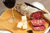 Salami and cheese on a wood table — Stock Photo