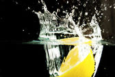 Lemon and water bubbles on a black background — Stock Photo