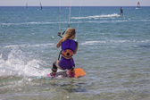A young girl with kite surfing — Stock Photo