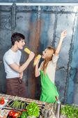 Unga roliga par leker med majskolvar — Stockfoto