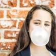 Stock Photo: Little Happy Girl Blowing a Chewing Gum
