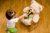 Little girl playing with a toy bear and tea things — Stock Photo