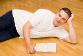 Young man lying on the floor and reading a book — Stock Photo