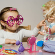 Little adorable girl playing with doll and toy sunglasses — Stock Photo