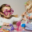 Little adorable girl playing with doll and toy sunglasses - Stock Photo