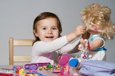 Little girl plays with a doll — Stock Photo