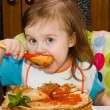 Little girl eating red caviar - Stock Photo