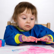 Foto Stock: Little girl stare with astonishment at color fingers