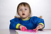 маленькая девочка живопись палец краски на бумаге и глядит — Стоковое фото