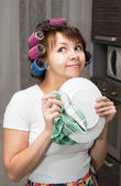 Housewife wipes plate and dreams in kitchen — Stock Photo